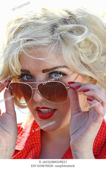 Blonde haired young woman looking over her sunglasses smiling