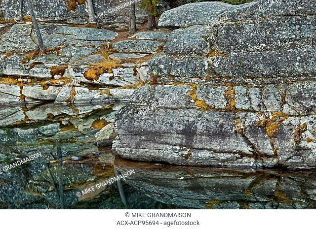 Rocky shoreline reflected in Horseshoe Lake Jasper National Park Alberta Canada