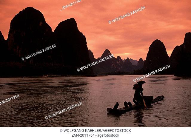 CHINA, GUANGXI PROVINCE, NEAR GUILIN, XING PING, LI RIVER, FISHERMAN ON BAMBOO RAFT, CORMORANTS