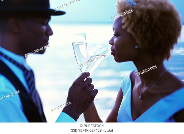 Side profile of a newlywed couple drinking champagne on the beach