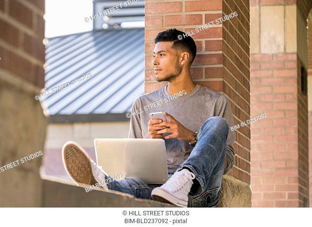Hispanic man leaning on brick pillar texting on cell phone