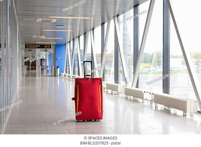 Suitcase in empty airport corridor