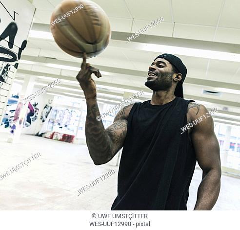 Smiling man with tattoos balancing basketball on his finger