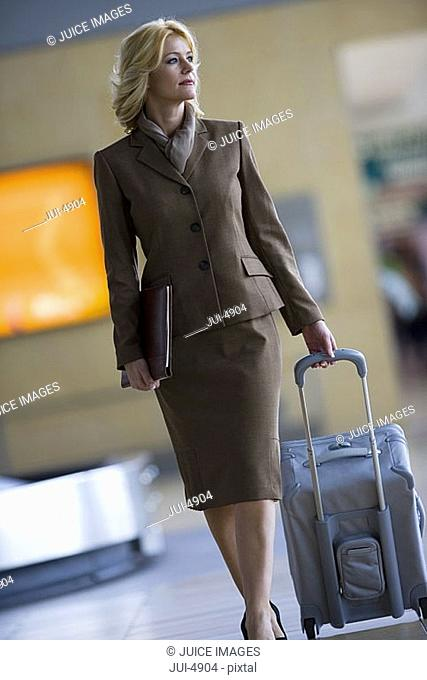 Businesswoman walking with luggage in airport baggage claim area, front view tilt