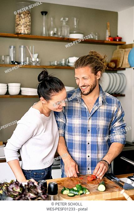 Young couple preparing food together, tasting spaghetti
