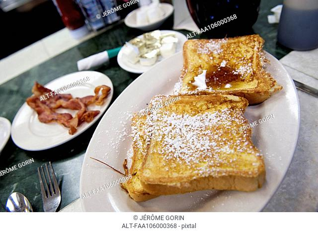French toast and bacon on restaurant table