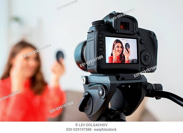 blogging, technology, videoblog and people concept - happy smiling woman or beauty blogger with eyebrow pencil, mirror and camera recording makeup tutorial...