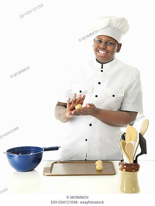 A young chef smiling at the viewer as he hand rolls dough into balls before placing them on the cookie sheet. On a white background with space on left for your...