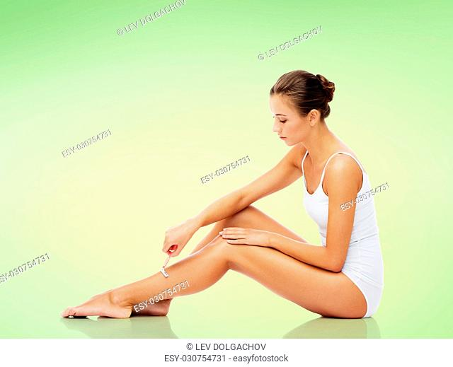 people, beauty and bodycare concept - beautiful woman with safety razor shaving legs sitting on floor over green background