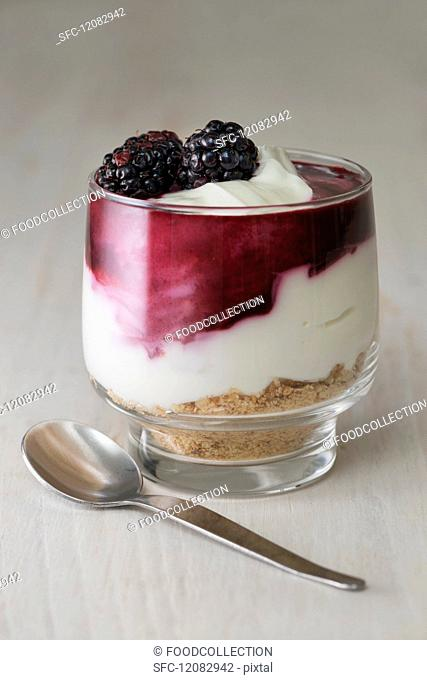 Blackberry cheesecake made withcream cheese, cream, blackberry coulis and crushed biscuits served in a glass