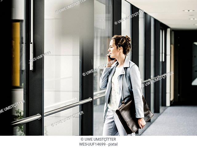 Businesswoman on cell phone looking out of window in office passageway