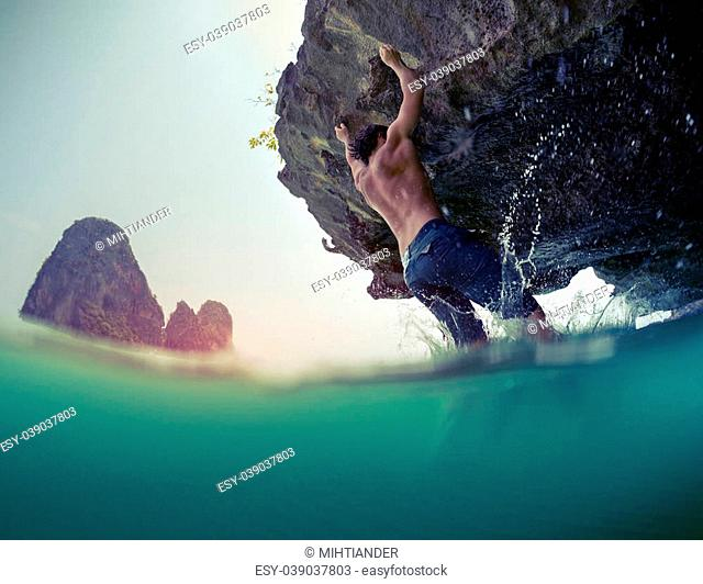 Young athlete trying to climb natural wall without belay. Deep water soloing
