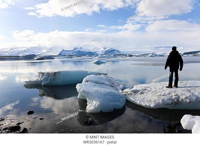 Rear view of person standing on ice sheet on glacial lagoon with icebergs, mountains in the distance