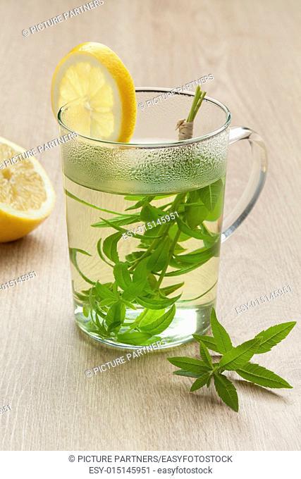 Glass with lemon verbena tea and lemon