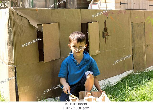 Portrait of boy painting against cardboard playhouse in back yard on sunny day