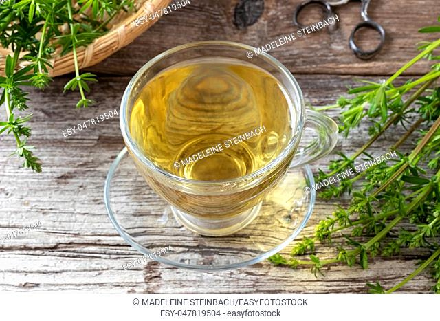 A cup of herbal tea with fresh bedstraw twigs
