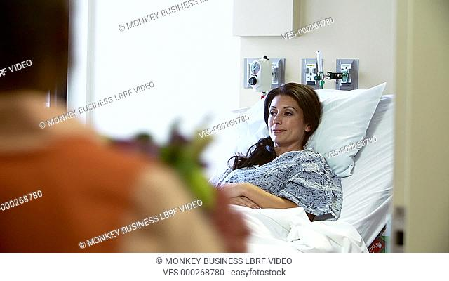 Hospital volunteer brings bunch of flowers to female patient in bed.Shot on Sony FS700 in PAL format at a frame rate of 25fps