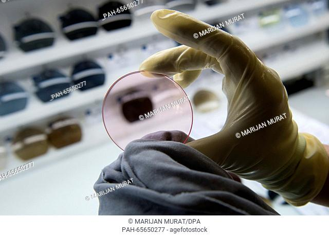 An employee of Carl Zeiss AG conducts a quality test on tinted glass in the dye-works of the eyeglass production in Aalen, Germany, 05 February 2016