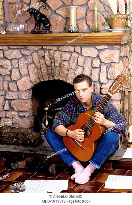 Italian singer-songwriter Eros Ramazzotti playing guitar seated beside a fireplace. Italy, 1986