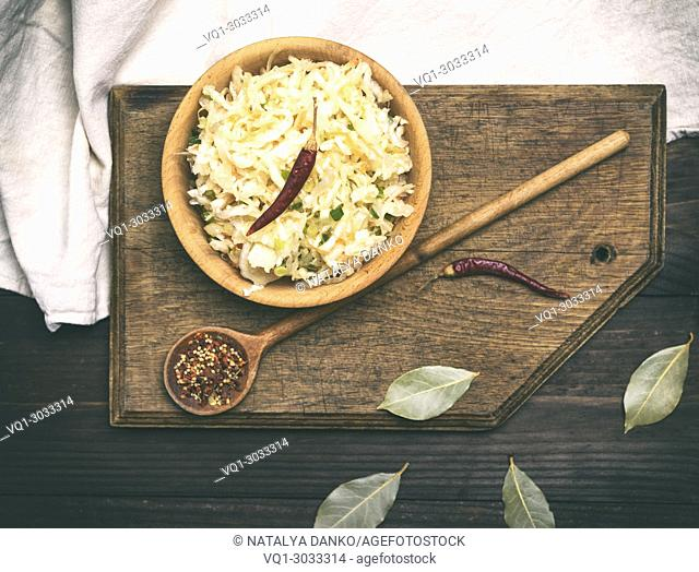 sauerkraut with carrots and green onions in a brown wooden bowl, vintage toning