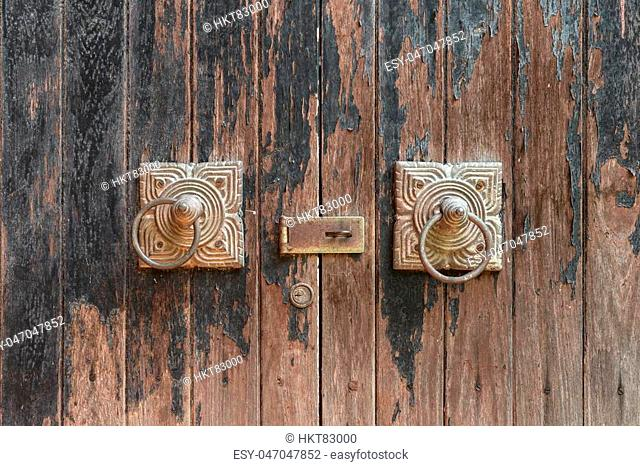 Ancient wooden gate with two door knocker rings, close up