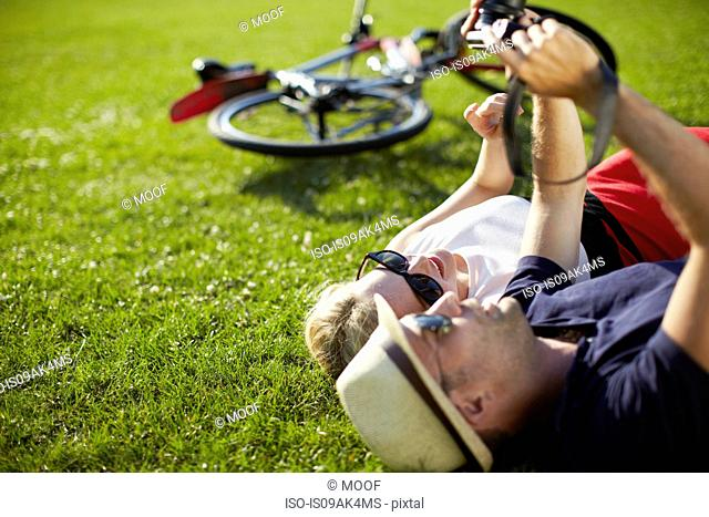 Couple lying in park looking at photographs on digital camera