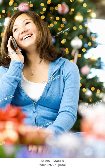 A girl by a Christmas tree, talking on a mobile phone