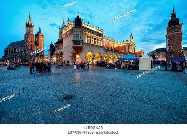 Main Square in the Old Town of Krakow in Poland at dusk. On the left St Mary Basilica, in the middle Cloth Hall (Sukiennice), on the right Town Hall tower