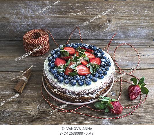 Rustic spicy ginger cake with cream-cheese filling, fresh strawberries and blueberries