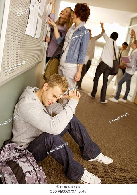 Frustrated man sitting near college students checking test scores in corridor