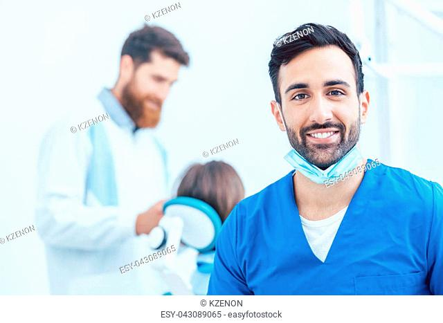 Portrait of a confident dental surgeon wearing blue protective uniform and surgical mask while looking at camera in a modern dental office with reliable...