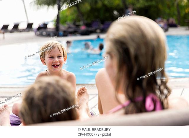 Mother and sons relaxing at poolside