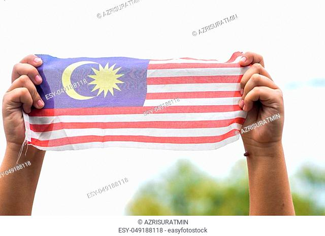 Hand waving Malaysia flag also known as Jalur Gemilang in conjunction with the Independence Day celebration or Merdeka Day