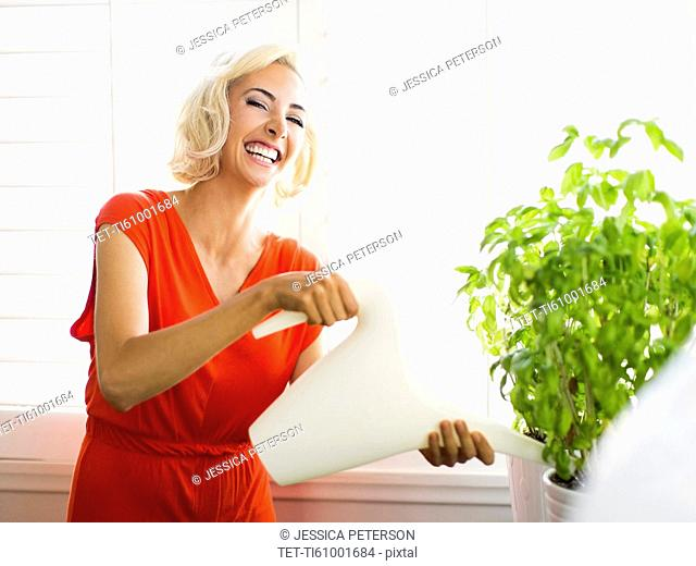 Woman in red dress watering potted plant