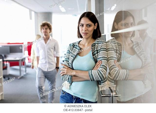 Portrait confident businesswoman leaning on glass in office corridor