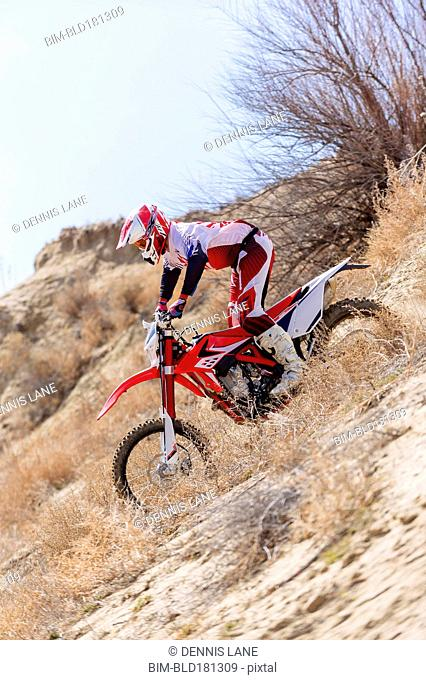 Motorcyclist riding dirt bike in remote field