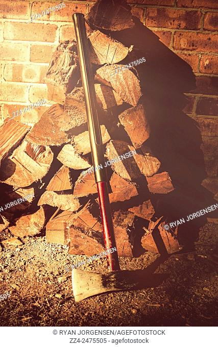 Afternoon still with filter of a wood chopping axe next to stacked timber. Country life details