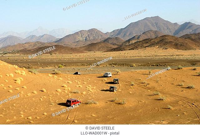 A Convoy of 4x4 Vehicles with The Hajar Mountains in Background  Wadi Al Abyad, Sultanate of Oman, Middle East