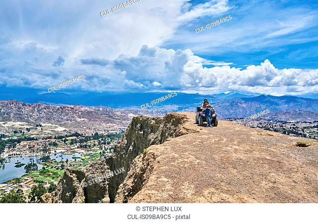 Mother and sons beside quad bike, on mountain top, La Paz, Bolivia, South America