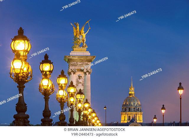 Row of lampposts along Pont Alexandre III with dome of Hotel des Invalides beyond, Paris, France