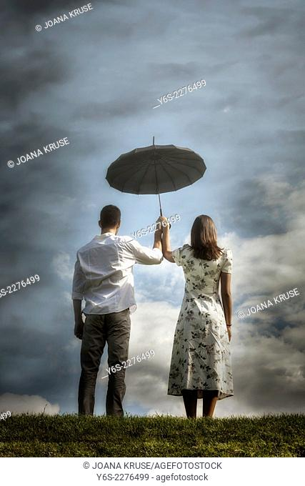 a couple on a meadow with an umbrella