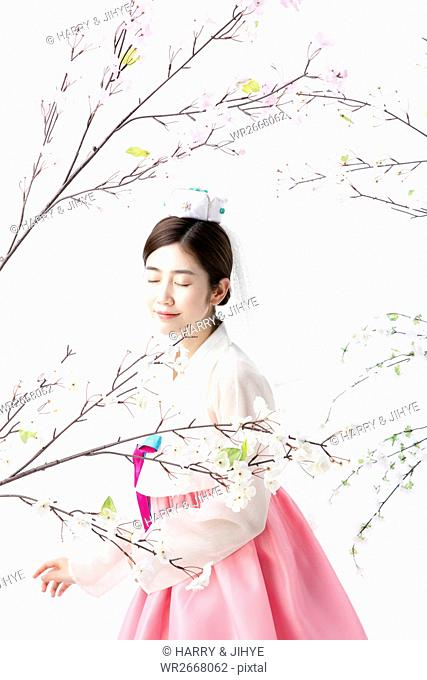 Young woman in traditional Korean clothes smelling spring flowers
