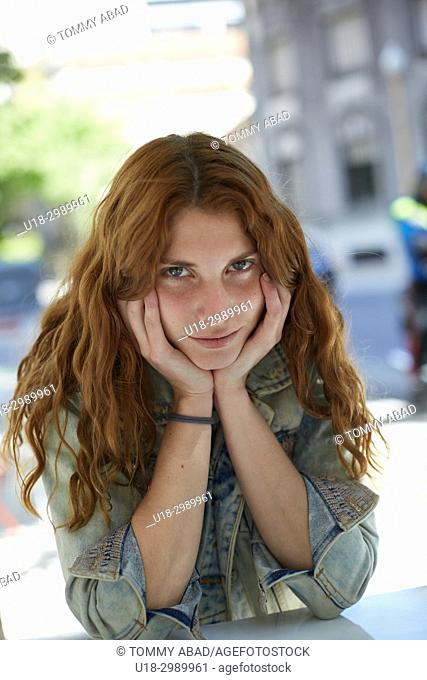Young redhead woman sitting out with hands in cheek