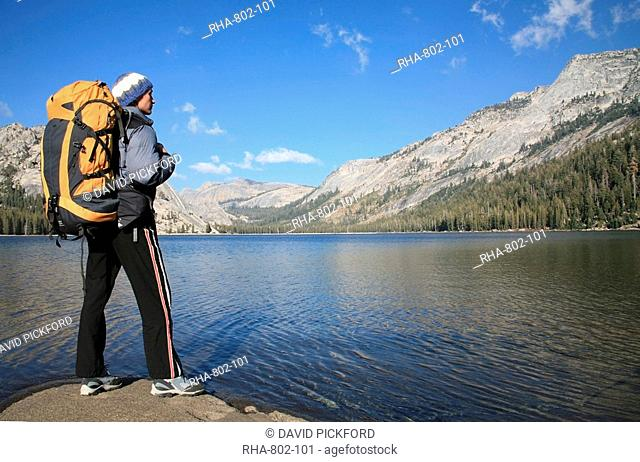A hiker takes in the view on the shore of Tenaya Lake, in the Tuolumne Meadows, near Tioga Pass and Yosemite Valley, Sierra Nevada, California