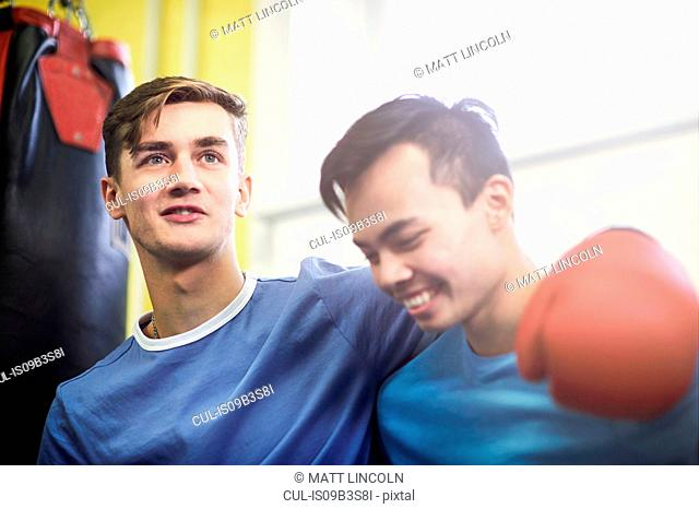 Two young male boxing friends in gym