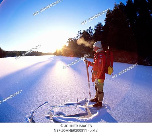Man standing on snowy ground with skis
