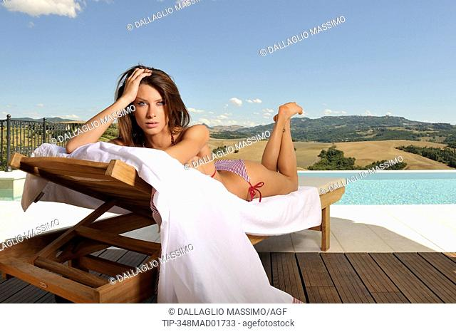woman at swimming pool relaxing in chair