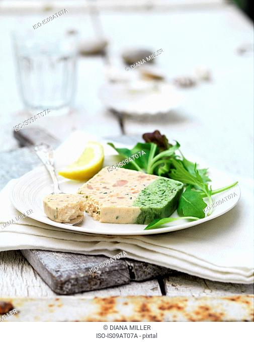 Still life of prawn and asparagus terrine slice and salad leaves with lemon