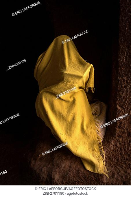 Ethiopia, Amhara Region, Lalibela, orthodox woman covered with a yellow shawl praying with a bible