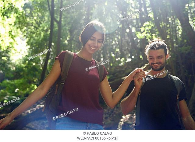 Spain, Canary Islands, La Palma, smiling couple walking hand in hand through a forest